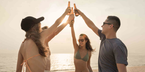 Bierabsatz in Deutschland gestiegen. Gruppe feiert am Strand mit Bier.
