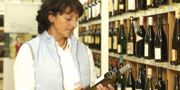 Frau kauft Wein im LEH